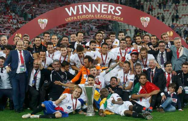 Sevilla's players pose with the trophy as they celebrate defeating Benfica in their Europa League final soccer match at the Juventus stadium in Turin May 14, 2014.              REUTERS/Albert Gea (ITALY  - Tags: SPORT SOCCER)